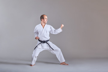 Sportsman in karategi and with a black belt does formal karate exercises