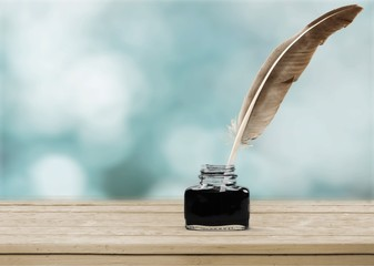 Feather quill pen and glass inkwell isolated on a white