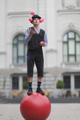 The clown juggles with pink balls, standing on a big red ball in the street of a European city