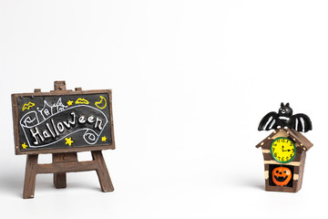 Brown label with a halloween text and halloween house with a yellow clock and center copy space.