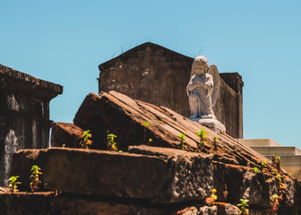 Angel statue on top of above ground graves in cemetery