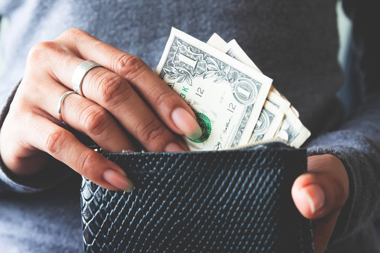 Paper currency in wallet with woman hands.