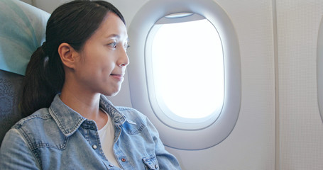 Woman looking out of window on plane