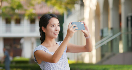 Woman taking photo on cellphone at outdoor
