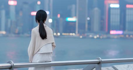 Wall Mural - Woman look far away of the city view in Hong Kong