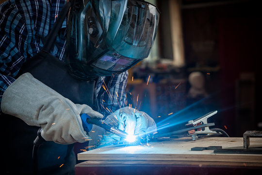 Strong man welder in work clothes hard working and welds with a welding machine metal . in the workshop