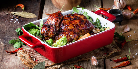 Baked chicken in glaze with vegetables in red form for baking on old wooden table, rustic style, selective focus