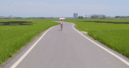 Woman walking though the road beside paddy rice field