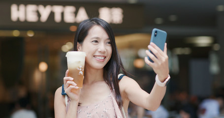 Woman holding a cup of cheese green tea and taking selfie on cellphone at Heytea store in the city