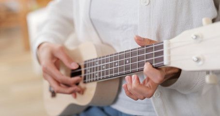 Woman play a music on ukulele