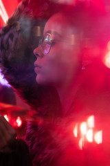 Young girl with glasses with trendy fur coat on neon lights