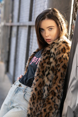 Young girl standing with fur coat on sunset