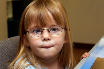Young Girl With Strabismus or Ocular Palsy Trying On A Pair Of New Glasses