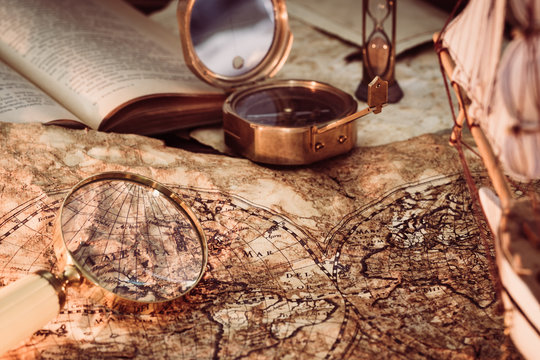 Old vintage maps and marine equipment like compass, magnifier or hourglass and ship. Columbus Day concept.