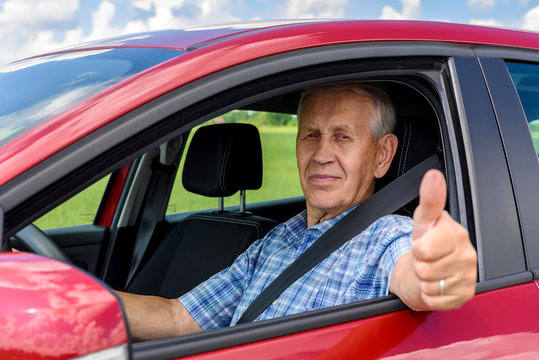 elderly man driving the car and shows the thumb