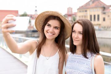 Young women taking selfie on city street
