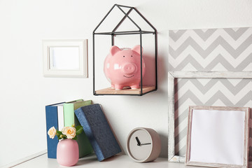 Cute piggy bank on shelf indoors. Stylish interior element
