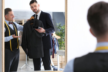 Tailor showing jacket to client in atelier