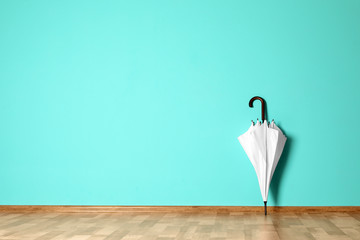 Wall Mural - Beautiful umbrella on floor near color wall with space for design