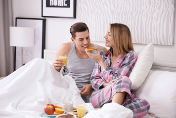Happy couple having breakfast together in bed