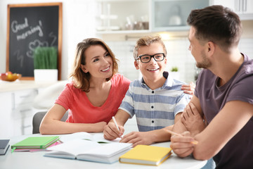 Teenager with parents doing homework at home