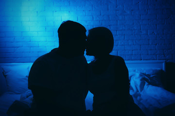 Silhouette of couple in bed at night time