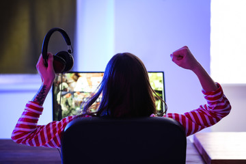 Young woman with headphones playing video games at tournament