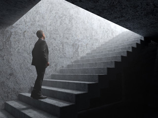 man climbs the stairs from darkness to light