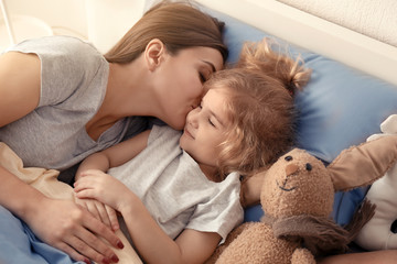 Mother kissing her sleeping daughter in bed at home. Family bedtime