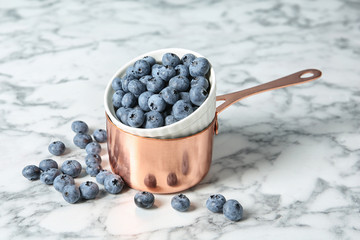 Cookware with juicy and fresh blueberries on marble table
