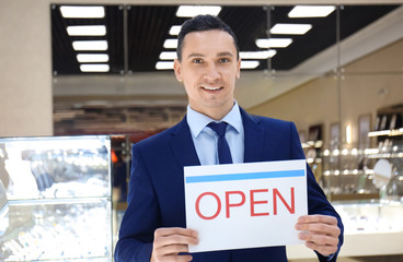 Portrait of young man with OPEN sign in jewelry store. Small business owner