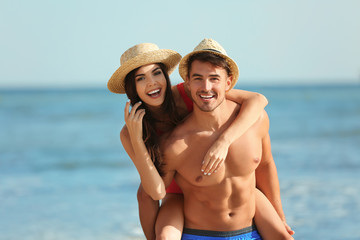 Happy young couple having fun at beach on sunny day Wall mural