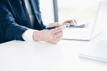 Businessman working, Hand holding pen and using laptop computer in modern office, Business and Office concept.