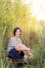 Beautiful young girl on the pier in the near green reeds