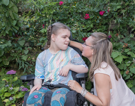 Disability a disabled child learning and communicating with help from a special needs care assistant