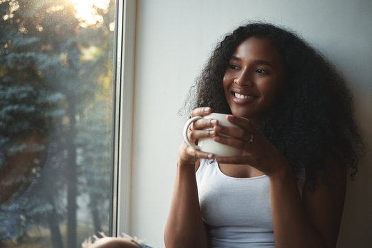 Close up view of fashionable cute young African American female in white tank top having rest indoors, holding large cup of hot tea, smiling broadly, daydreaming, spending nice time at home alone