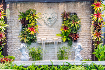 Statue lion on stone wall in garden./ Statue marble lion on stone wall and waterfall in cozy home flower garden on summer.