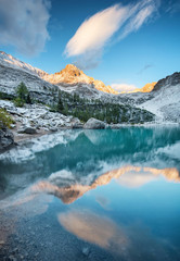 Sorapis lake in the Dolomite Alps, Italy. Mountains and reflection on the water surface. Natural landscape during sunrise in the Italy mountains.