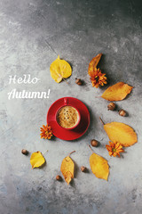 Red cup of black coffee with foam decorated by yellow autumn leaves, aster flowers and acorns over grey texture background. Flat lay, space. Seasonal background. Text hello autumn