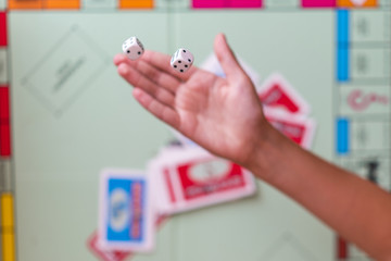 The hand throws game dice on the background of the playing field.