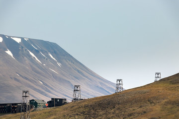 Old wooden pylons for coal-transport carts cables at the edge at Longyearbyen, Svalbard.