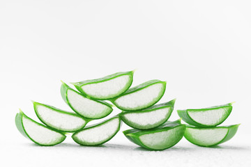 Fresh aloe vera slices with gel on white background.