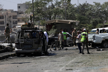 Free Syrian Army members (FSA) inspect damaged cars after a car bomb in Azaz