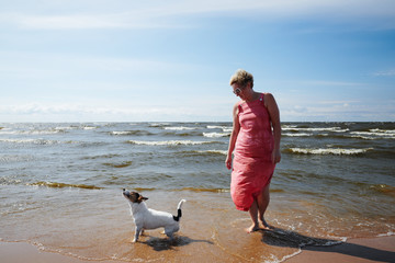 Adult female in pink dress and funny dog standing in waving water of sea on cloudy day
