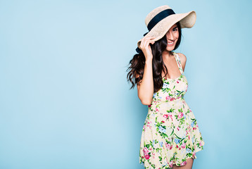 Portrait of cute summer brunette woman in hat and colorful dress, stylish girl have a fun and posing on blue background