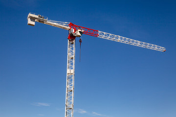 Tower crane against the blue sky - construstion concept