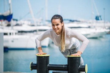 Sportive caucasian woman in white sportswear training outdoors doing crossfit exercise at sea jetty with marina and sailboats