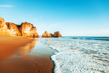 Wall Mural - beautiful ocean landscape, the coast of Portugal, the Algarve, rocks on the sandy beach, a popular destination for travel in Europe