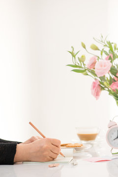 Female hand writing in a notebook at the desk, top view. On the white table lay flowers