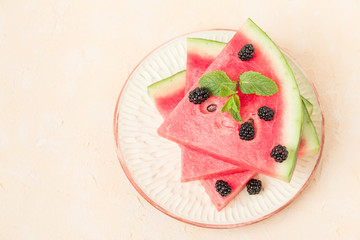 Watermelon slice pie with blackberries and mint leaf on pastel yellow background with copy space.